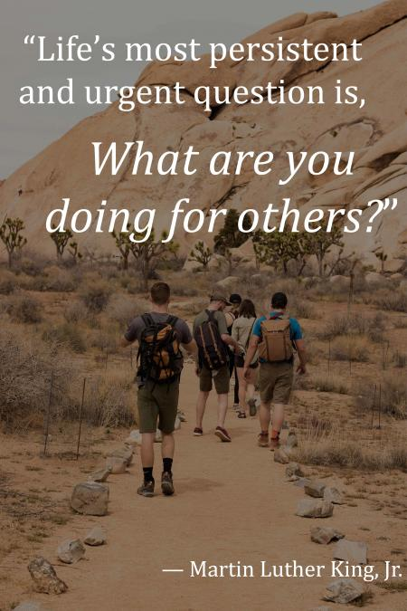 """five persons walking on pathway with the text """"life's most persistent and urgent question is, what are you doing for others?"""""""